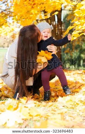 Young happy mother with daughter in autumn park - stock photo