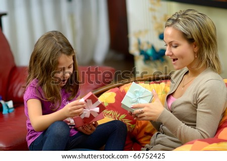 young happy mother with her daughter changing gift boxes - stock photo
