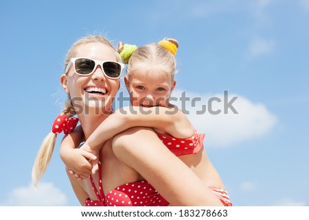 Young happy mother with little girl on her back. Happy family resting at beach in summer - stock photo