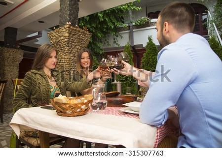 Young happy people toasting with wine and celebrating during a lunch in a restaurant. - stock photo