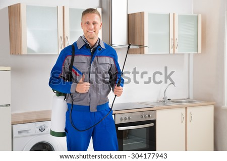 Young Happy Pest Control Worker With Insecticide Sprayer In Kitchen Room - stock photo