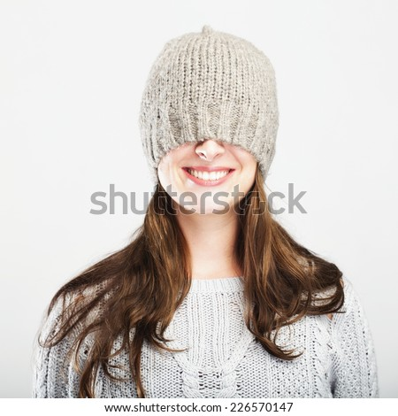 young happy playful cute winter girl covers eyes with hat, isolated on grey background - stock photo