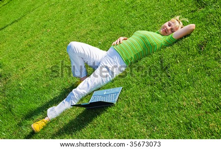 young happy pregnant woman lies on green meadow - stock photo