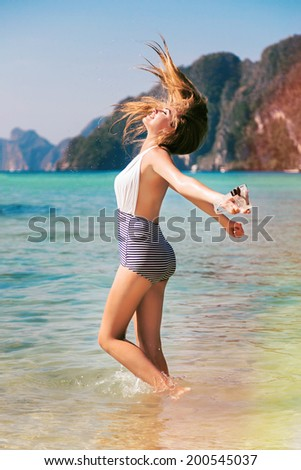 Young happy pretty blonde girl on vacation jumping in clear blue ocean water and enjoy freedom and summer time. Holding snorkeling  mask in her hand. Tropical island Phi Phi, Thailand. Bright colors. - stock photo