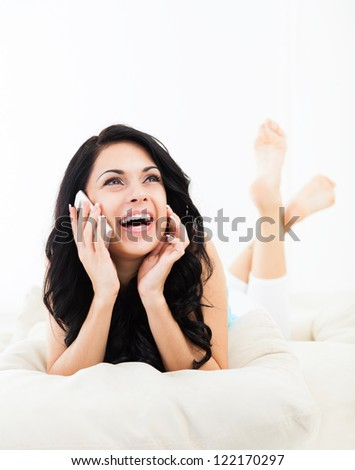 Young happy smile woman phone call on sofa in living room, at home - indoors, excited girl lying talking cellphone - stock photo