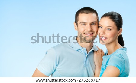 Young happy smiling amorous attractive couple, against blue sky background, with blank copyspace area for text or slogan - stock photo