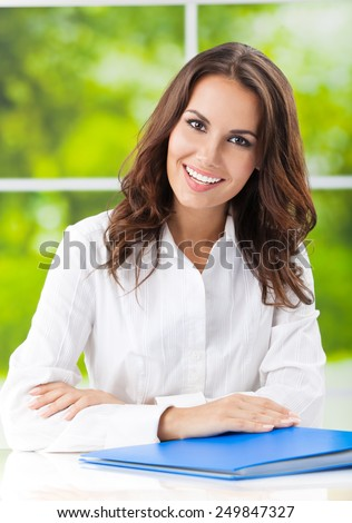 Young happy smiling attractive businesswoman at office - stock photo