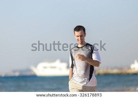 Young happy smiling attractive man holding smartphone, using app, making call, typing or reading message, dialing number, walking at sea shore from white yacht - stock photo