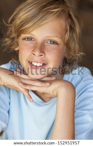 Young happy smiling blond boy child aged about twelve or early teenager resting on his hands - stock photo