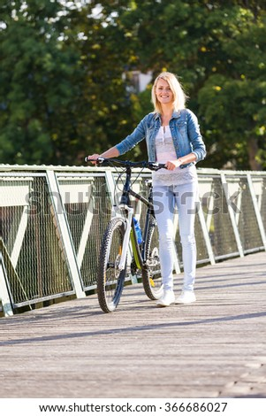 young happy smiling blonde beautiful woman wearing in white jeans riding bikes in park in bright sunlight on summer day - stock photo