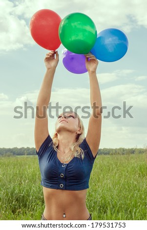 Young happy smiling blonde woman with balloons - stock photo