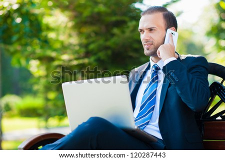 Young happy smiling business man working with laptop and cellphone, outdoors - stock photo