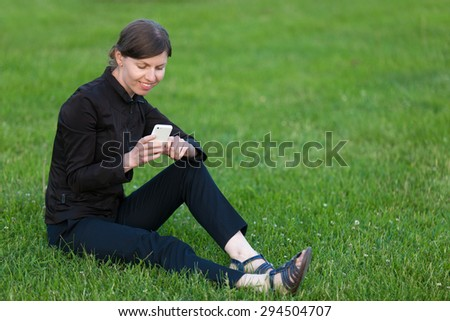 Young happy smiling business woman resting on break, sitting on grass on lawn, holding cellphone, looking at screen, using app, messaging, copy space - stock photo
