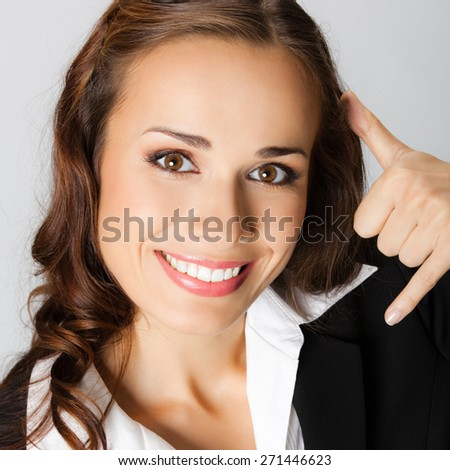 Young happy smiling businesswoman with call me gesture, against grey background - stock photo