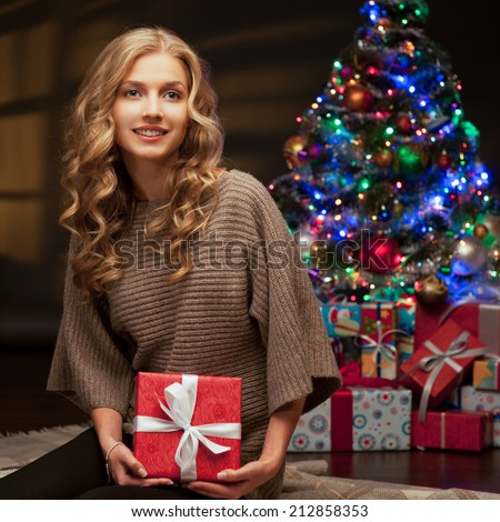 young happy smiling casual woman holding red gift over christmas tree and lights on background. warm light - stock photo