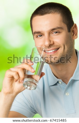 Young happy smiling man drinking water, outdoors - stock photo