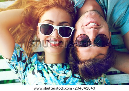 Young happy smiling pretty couple posing in hot summer day, wearing retro sunglasses, blonde beautiful girl and her handsome boyfriend. - stock photo