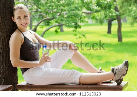 Young happy smiling sport fitness woman outside at summer - stock photo