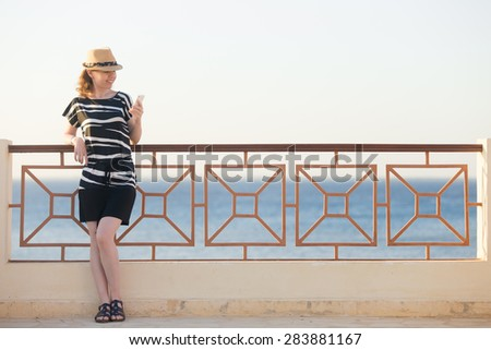 Young happy smiling woman in cute straw hat and casual summer dress standing on sunny street of sea town, holding cellphone, looking at screen, using app, messaging - stock photo