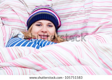 Young happy smiling woman in winter hat wrapped in duvet. - stock photo