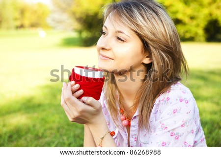 Young happy smiling woman with cup outdoors - stock photo