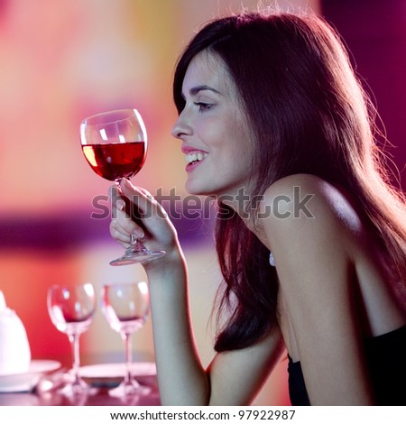 Young happy smiling woman with glass of redwine at restaurant or club - stock photo