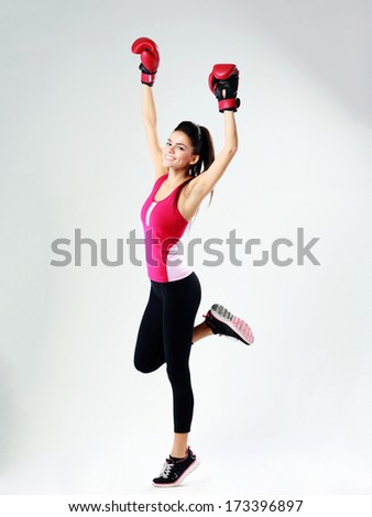 Young happy sports woman standing in boxing gloves on gray background - stock photo