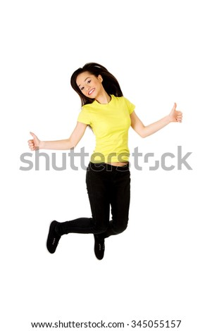 Young happy student woman jumping showing thumbs up. - stock photo
