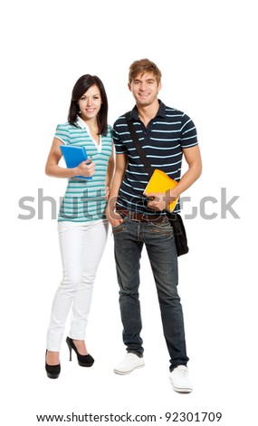 Young happy students couple smiling, holding notebooks standing full length portrait, looking at camera, isolated over white background - stock photo