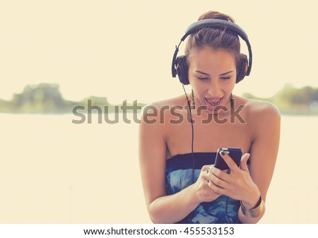 Young happy surprised woman with headphones listening to music on her smart phone outdoors by the lake in park  - stock photo