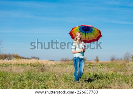 Young happy teenage girl with colorful umbrella posing on empty autumn field copy space background - stock photo