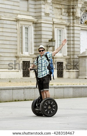 young happy tourist man with backpack riding city tour segway driving happy and excited visiting Madrid palace in Spain having fun in urban transport concept - stock photo