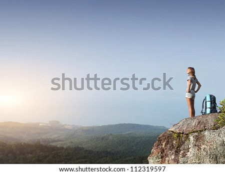 Young happy tourist with backpack standing on top of a mountain and looking to a sky - stock photo
