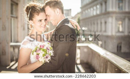 Young happy wedding couple bride meets groom on a wedding day. Happy newlyweds on terrace with gorgeous view. Portrait of loving young bride and groom. - stock photo