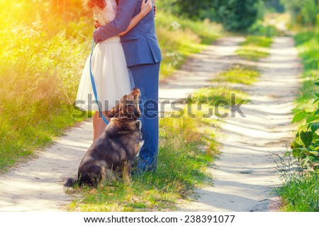 Young happy wedding couple hugging in the forest. Dog sitting near the couple. - stock photo