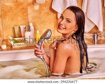 Young happy wet woman take bubble  bath. - stock photo