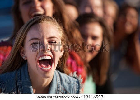 Young happy white teenage girl shouting with friends - stock photo