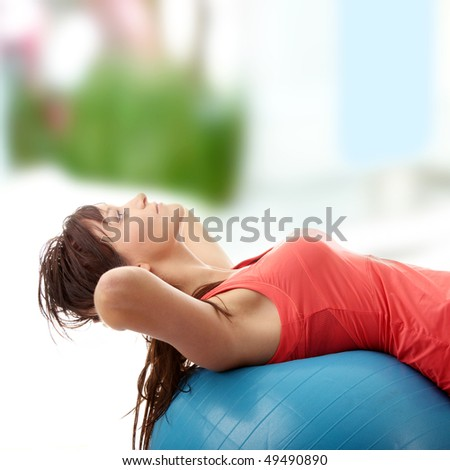 Young happy woman doing fitness exercise at home - stock photo