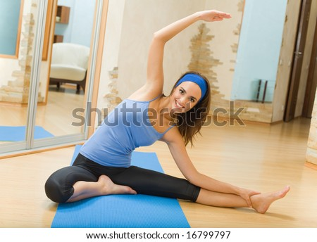 Young happy woman doing fitness exercises at home - stock photo