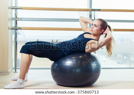 Young happy woman doing fitness exercises with fit ball at home - stock photo