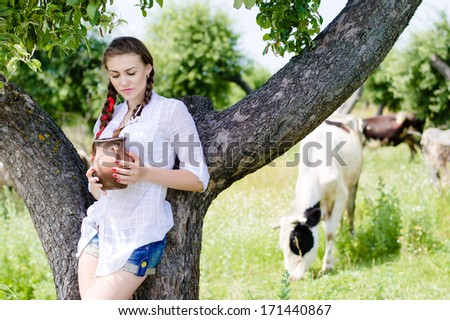 Young happy woman drinking fresh milk near cows in countryside - stock photo