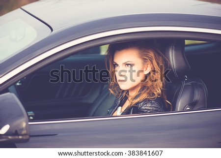 Young happy woman driving a sport car  - stock photo