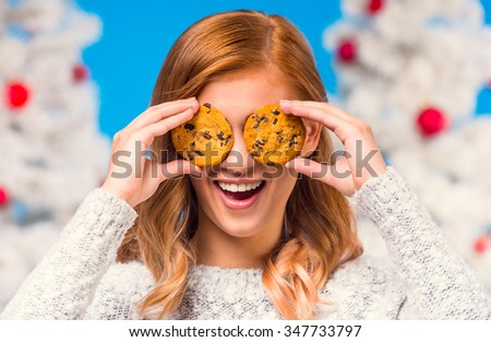 Young happy woman eating biscuits, during the celebration of Christmas, Christmas tree background - stock photo