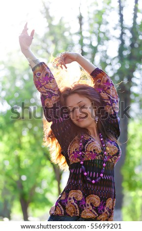 Young happy woman enjoys sun at park - stock photo
