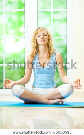 Young happy woman exercising at home - stock photo