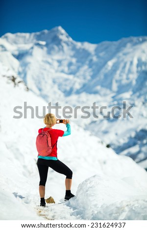 Young happy woman hiker taking photos on mountain peak summit in winter mountains. Climbing inspiration and motivation, beautiful landscape. Fitness healthy outdoors activity in Himalayas, Nepal - stock photo