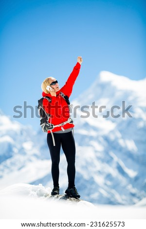 Young happy woman hiker talk on the phone on mountain peak summit in winter mountains. Climbing inspiration and motivation, beautiful landscape. Fitness healthy outdoors activity in Himalayas, Nepal - stock photo