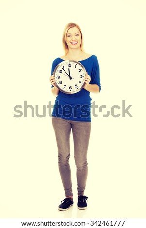 Young happy woman holding a clock.  - stock photo