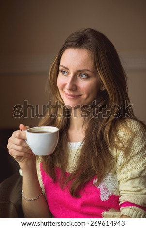 Young happy woman holding a cup of hot coffee or tea, sitting in a cafe looking out the window, lifestyle, breakfast or dinner to spend time relaxing, healthy lifestyle, fashion, in a yellow sweater. - stock photo