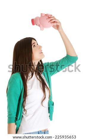 Young happy woman holding piggybank - stock photo